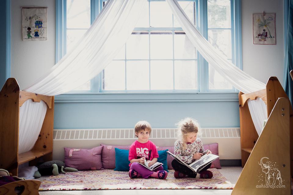 two preschoolers reading in a quiet room