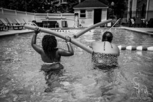 mother and daughter play in the pool