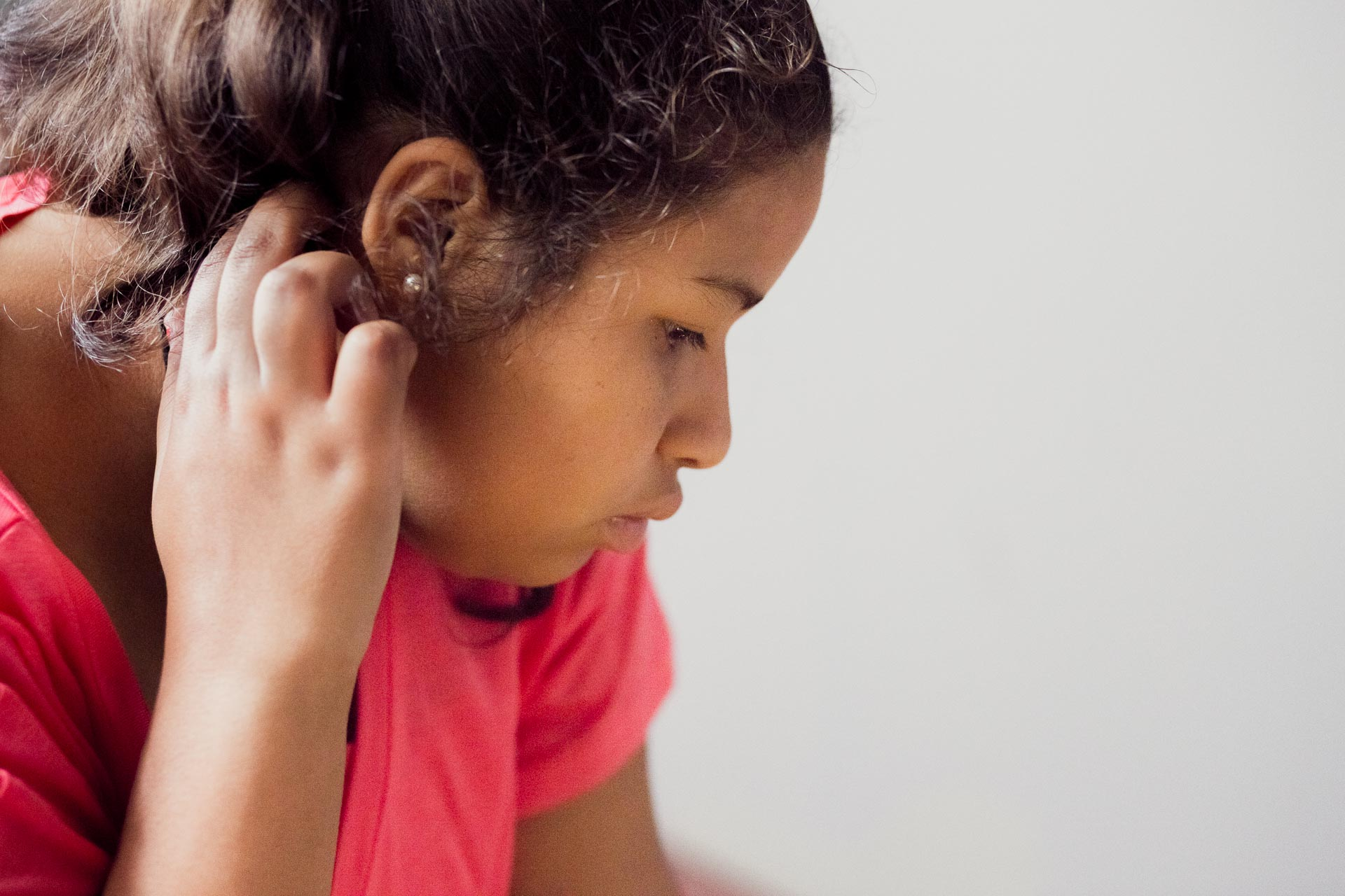 Veronica tucks her hair behind her ears