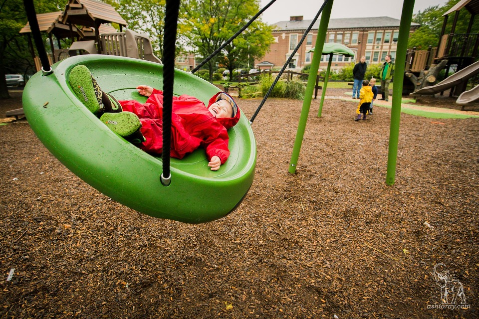 A toddler enjoys a platform swing in hte rain