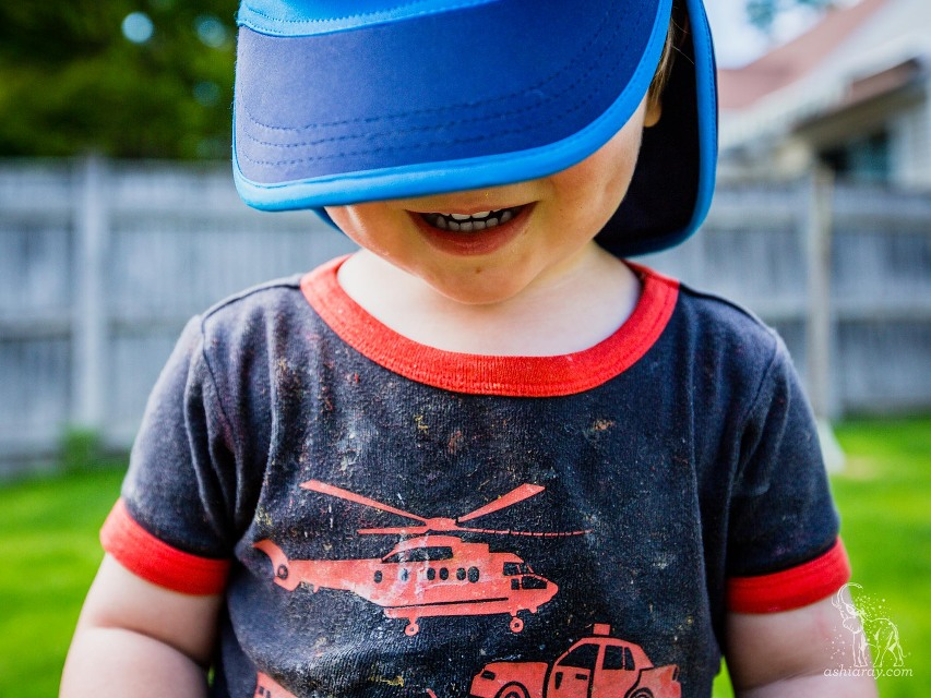 toddler with dirty shirt smiling under a blue hat