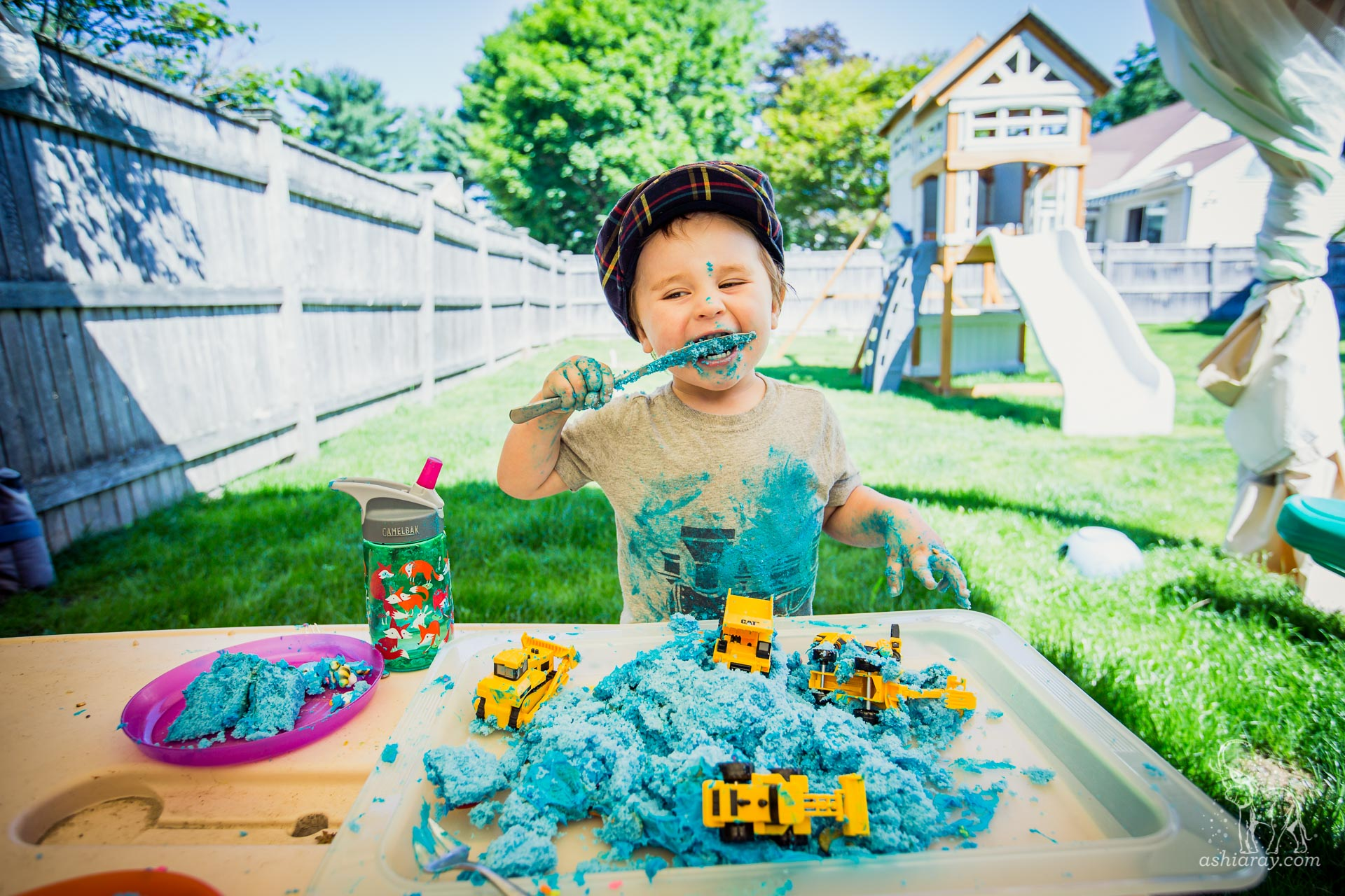 two year old eating blue cake with trucks