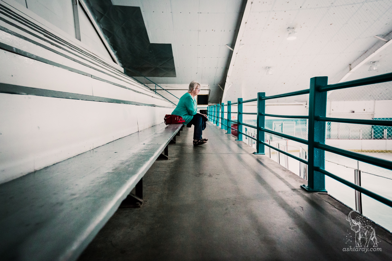 Grandmother sitting alone in hockey rink