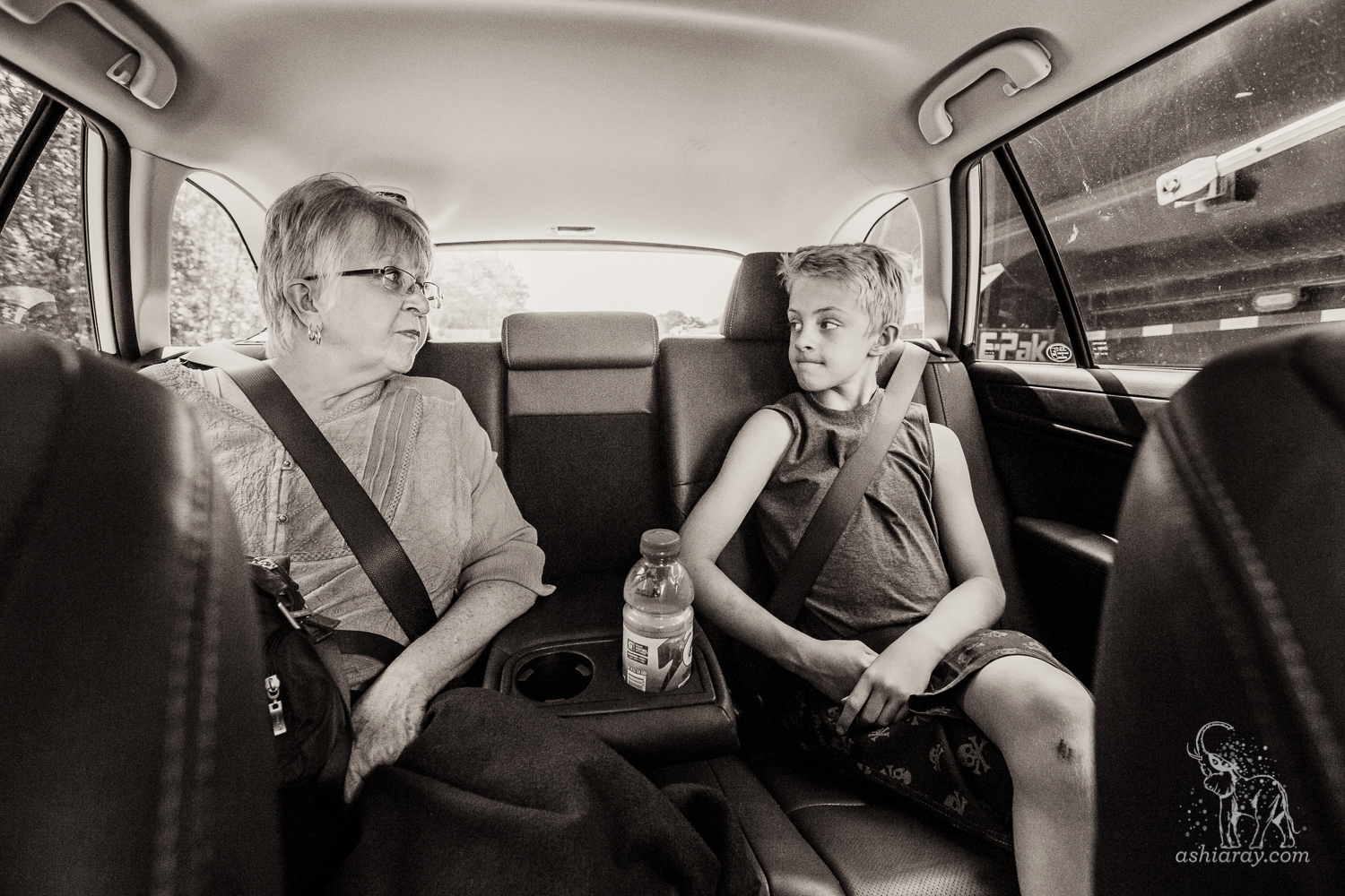 Grandmother and grandson in backseat of vehicle