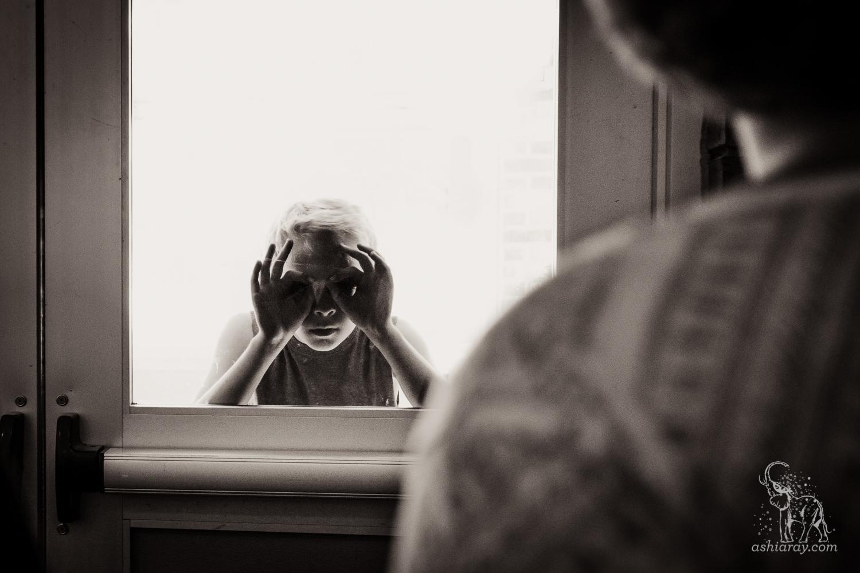 Boy peers through glass door into dark interior