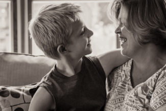 blonde 10 year old boy and mother smile at each othe