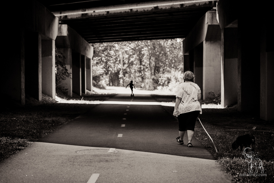 Mother walking dog approaches son silhouetted in the distance, bike path