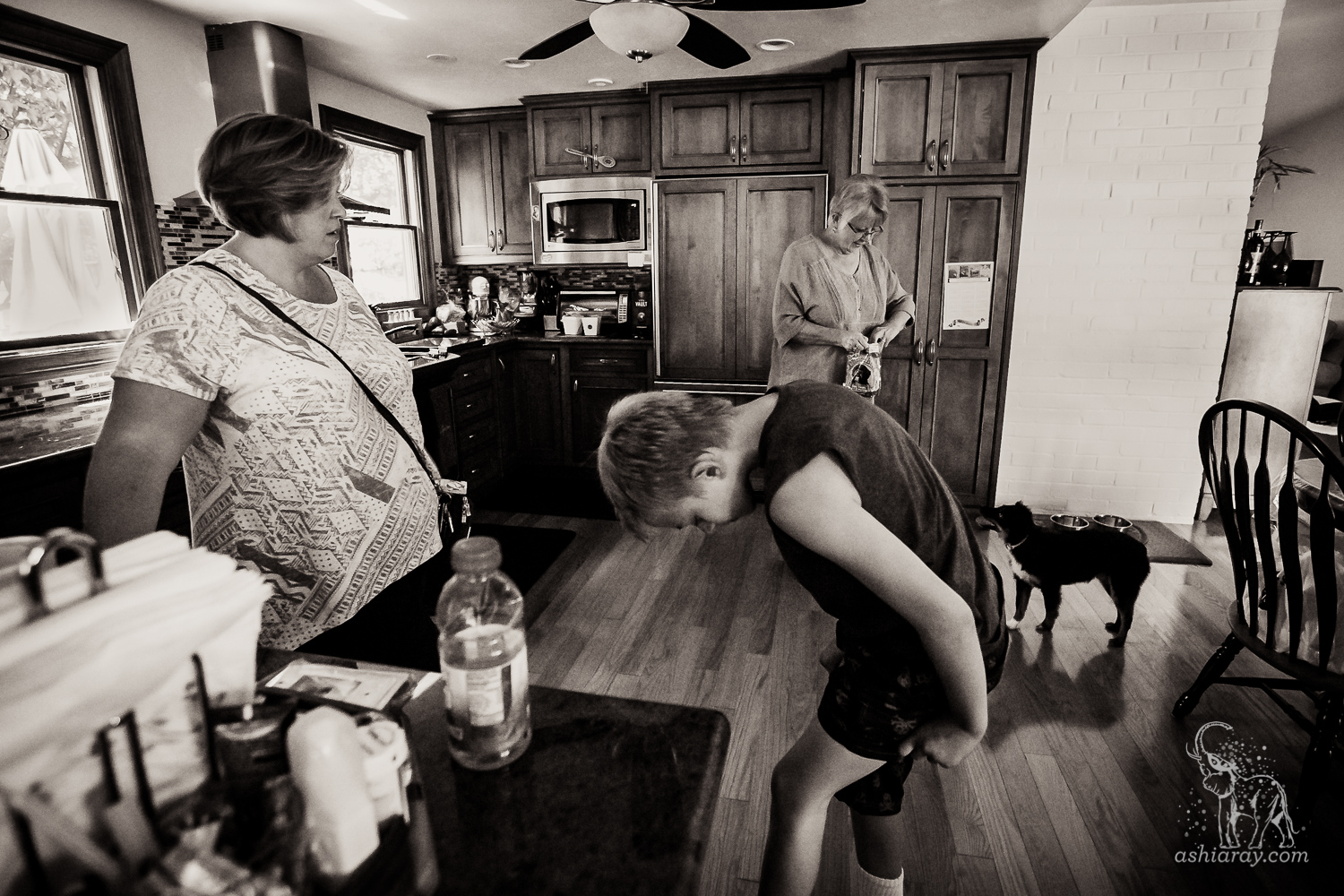 Grandmother, mother, son, and dog in kitchen