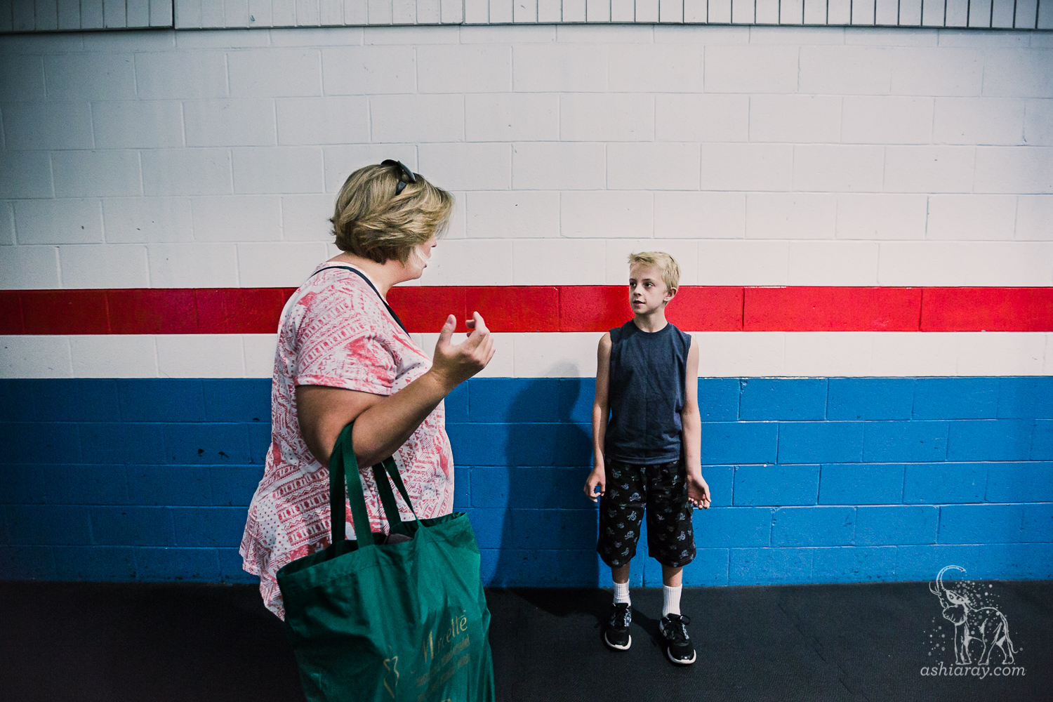 Boy and mother talking in front of wall with blue, red, and white stripes