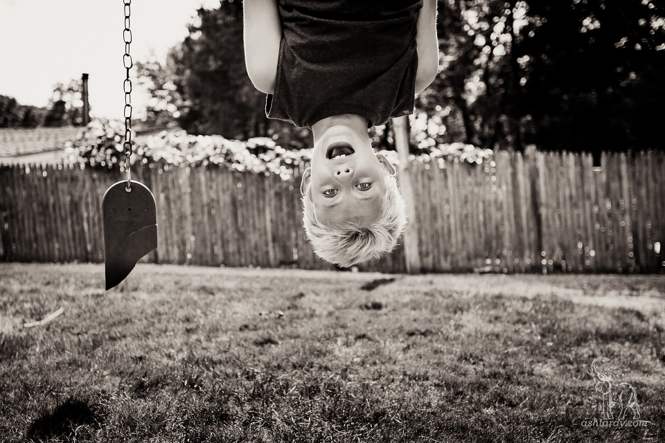 Boy hanging upside down from broken swingset