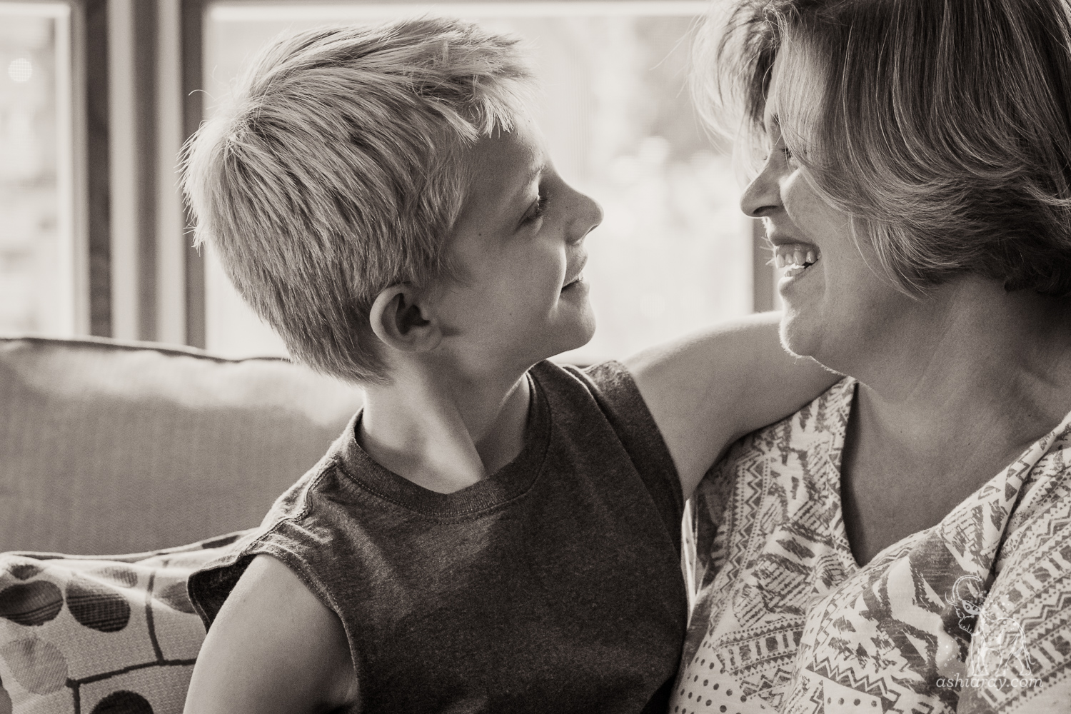Head & shoulders portrait of son and mother smiling at each other