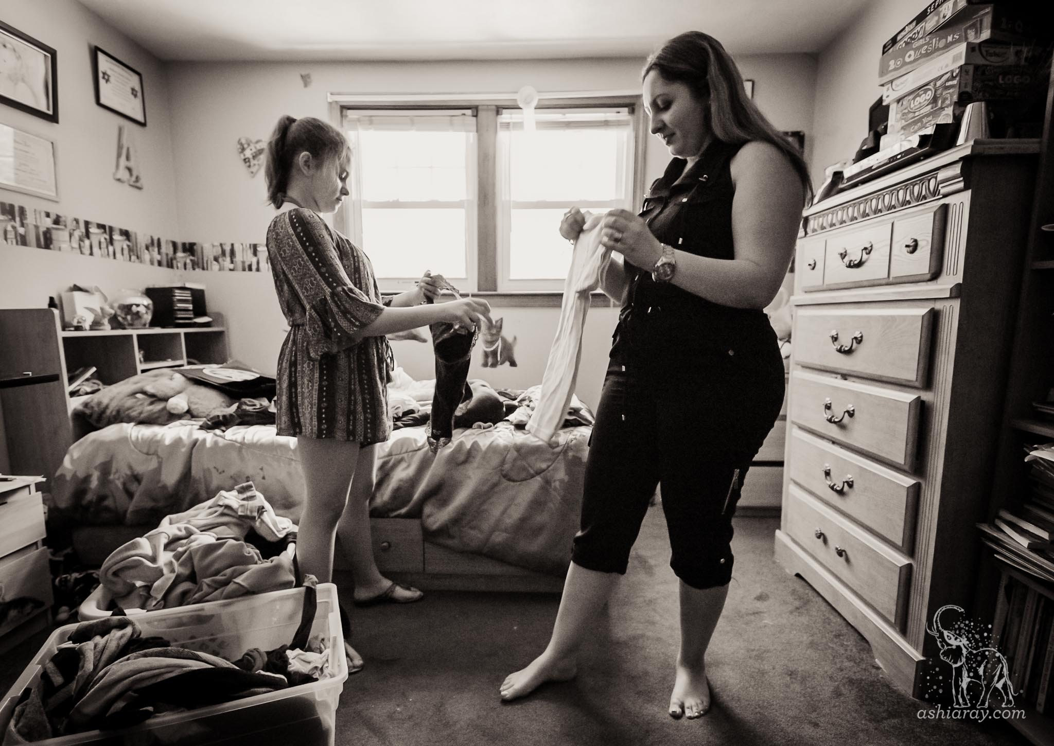 Mother and teen daughter fold laundry