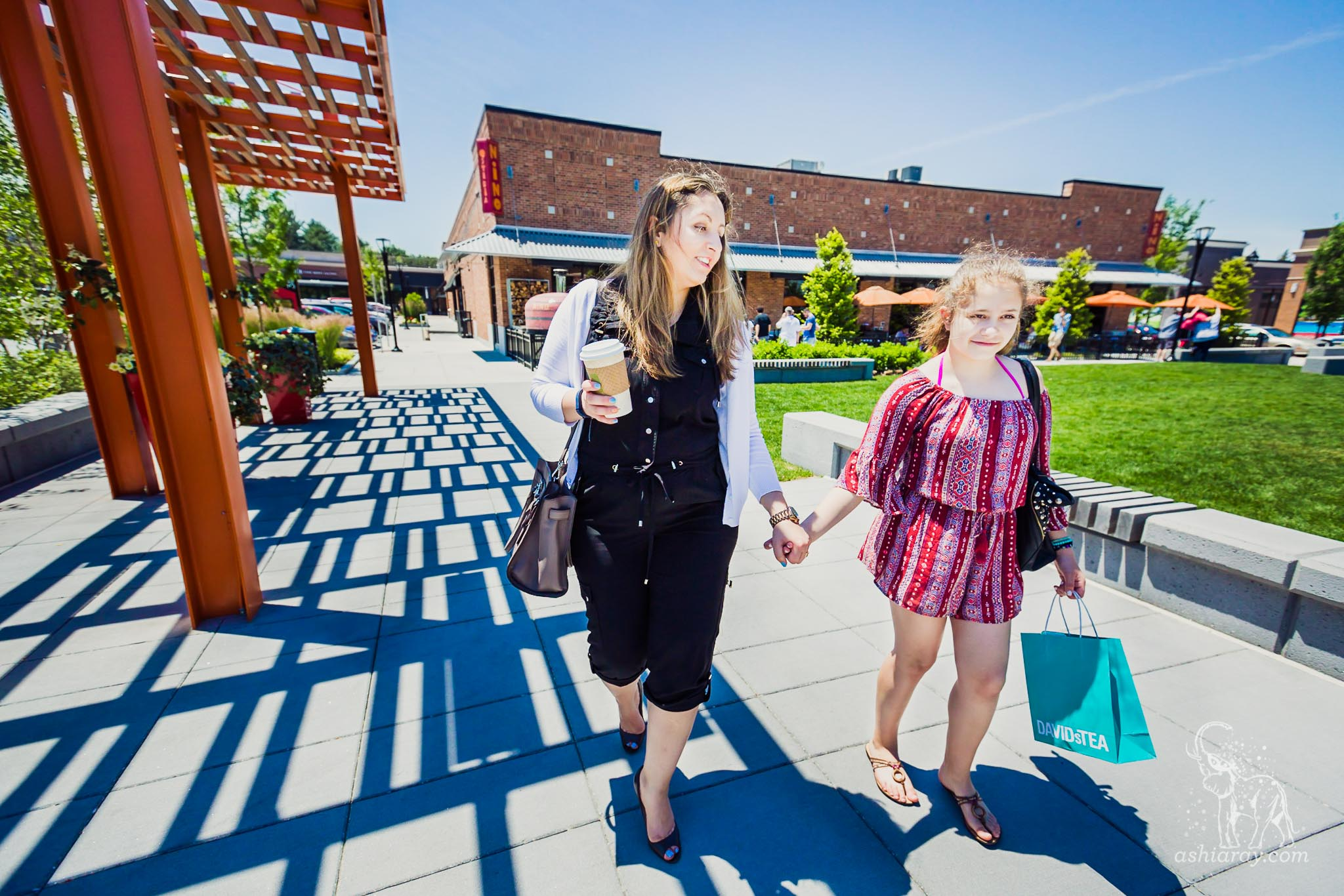 Mother and daughter walk in outdoor mall beside pergola shade