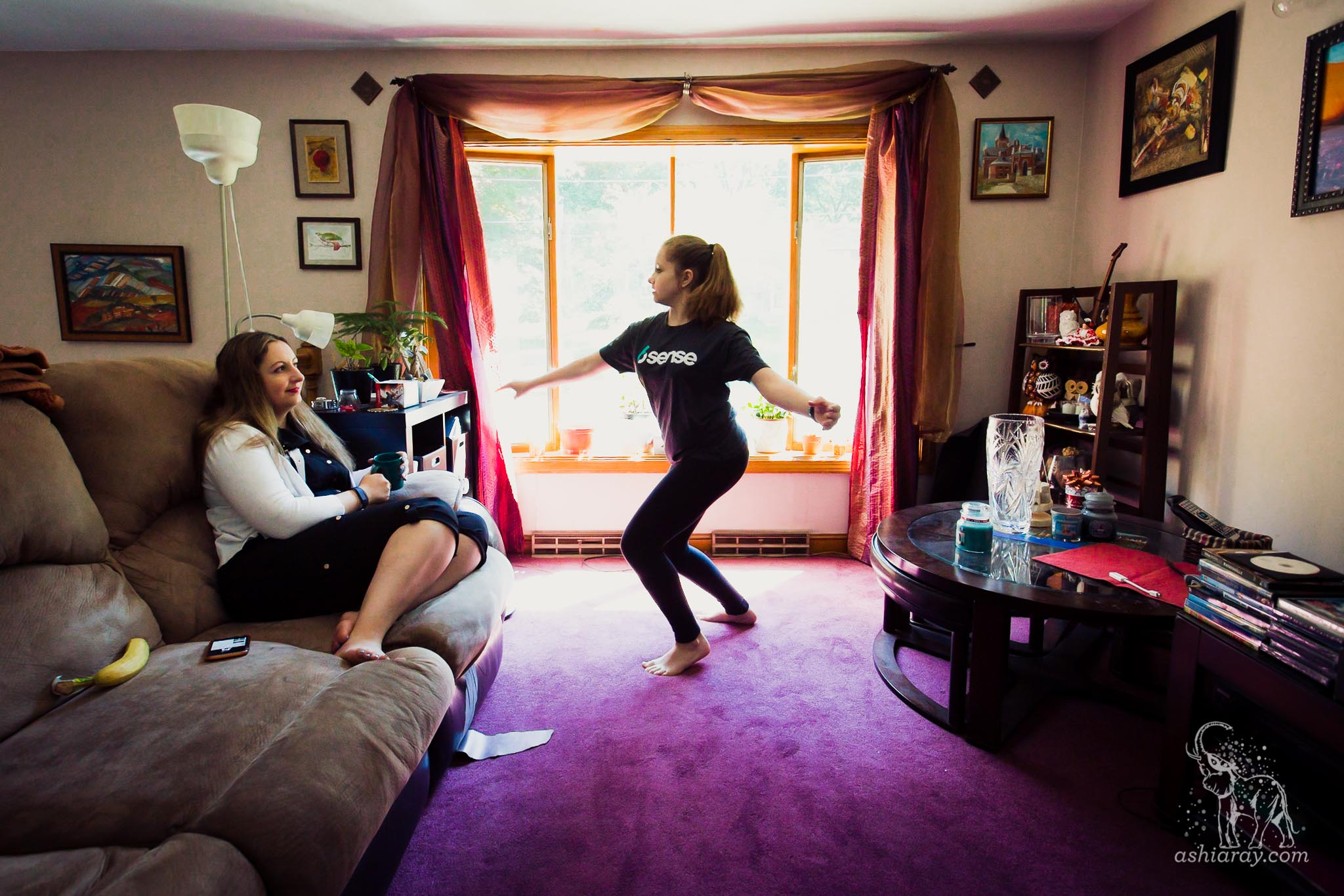 Teen girl dances in living room with purple rug