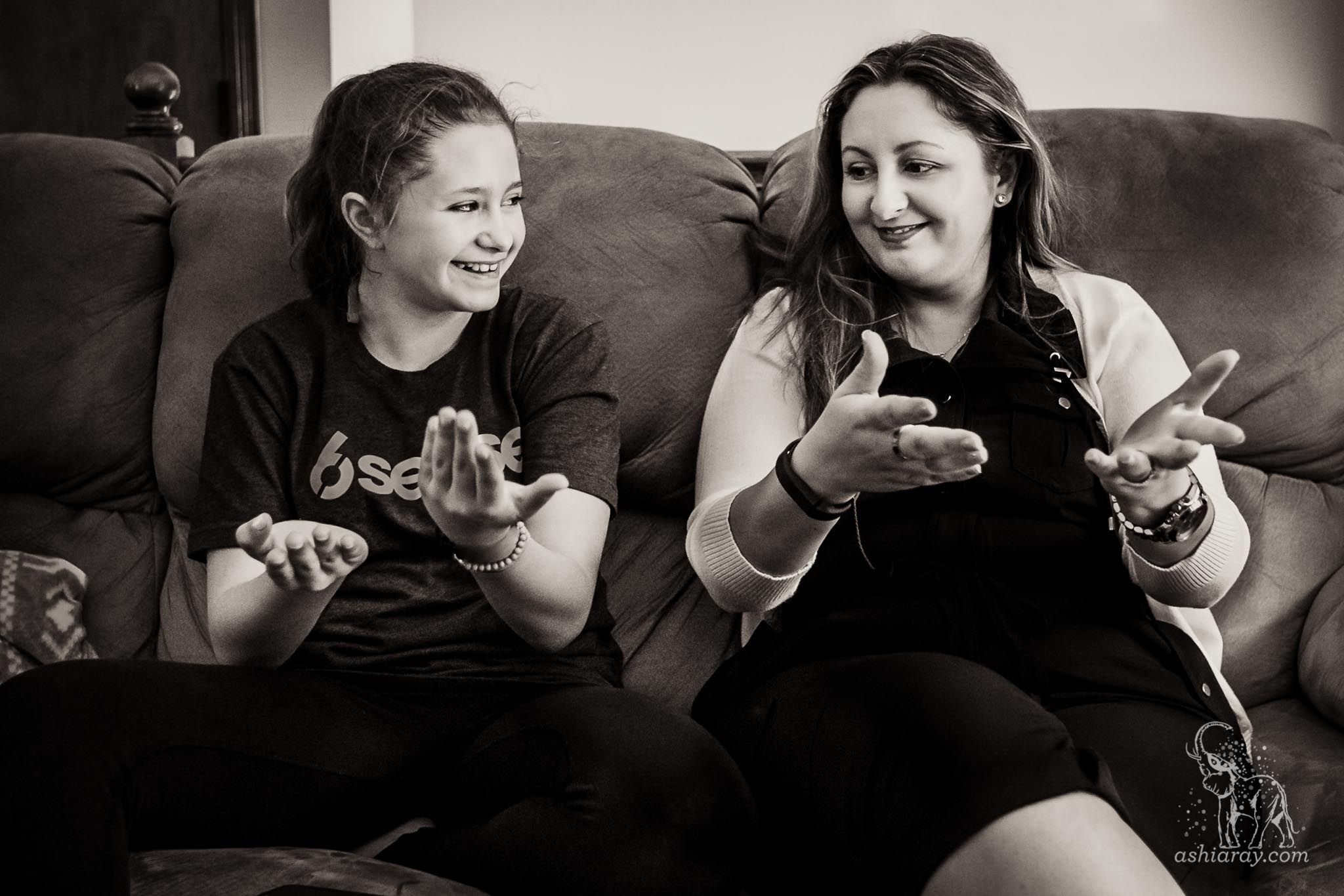 Mother learning hand coreography from teen daughter on sofa