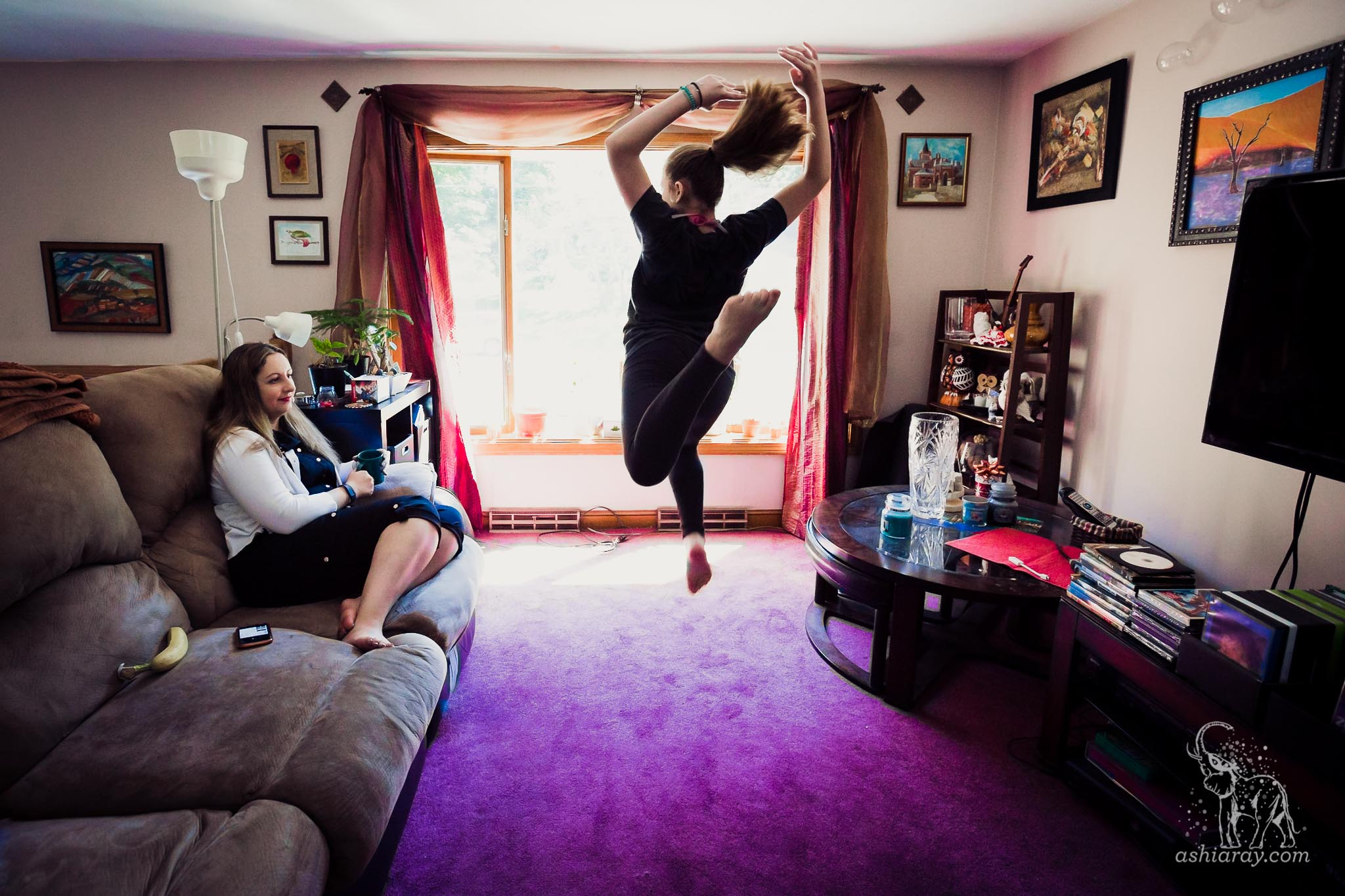 Mother watching teen daughter dance in living room with purple rug