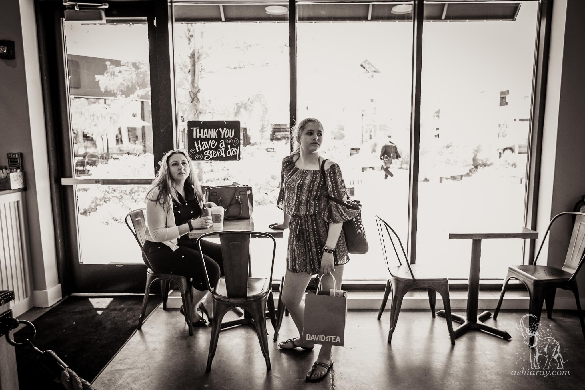 Mother and daughter in restaurant with shopping bags