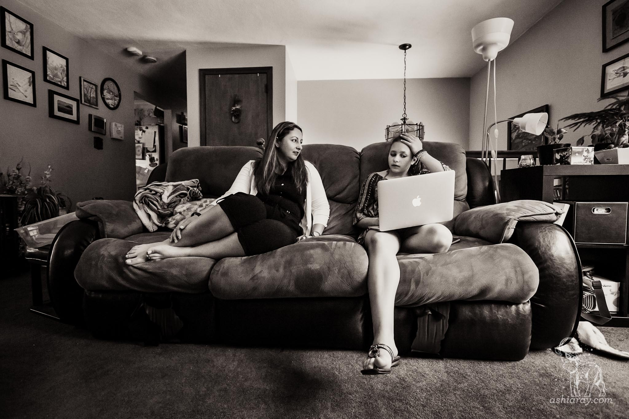 Mother and daughter talk on the sofa while using a laptop computer
