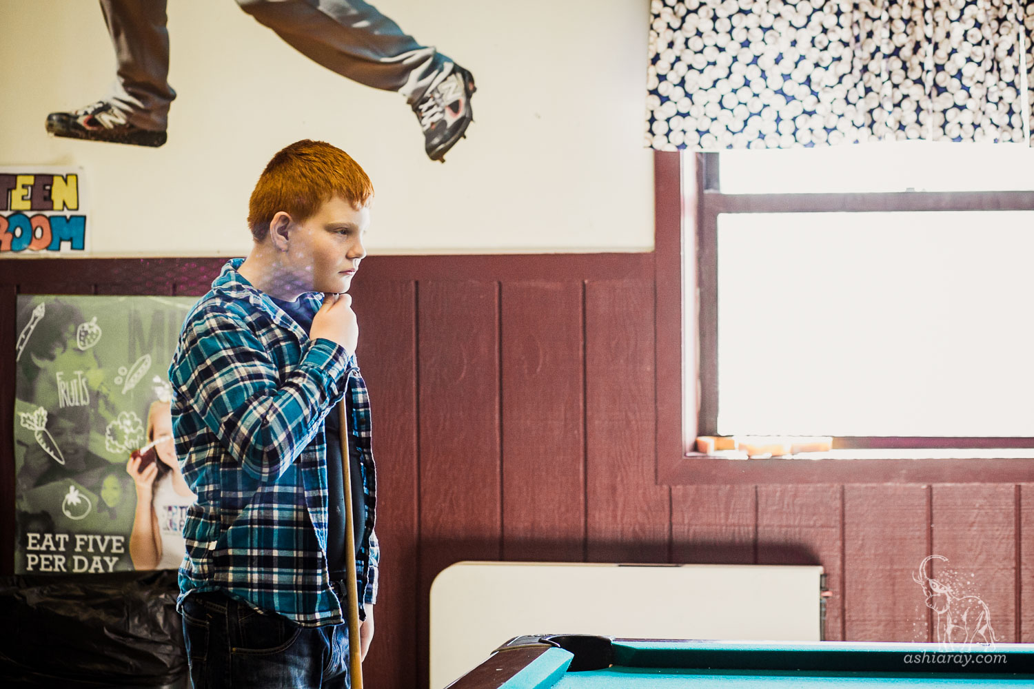 13-year-old boy in blue plaid shirt waiting his turn to play pool