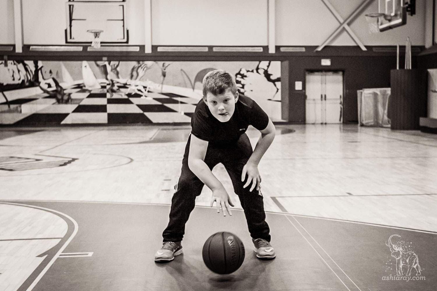 13-year-old boy dribbles a basketball, tounge poking out in concentration